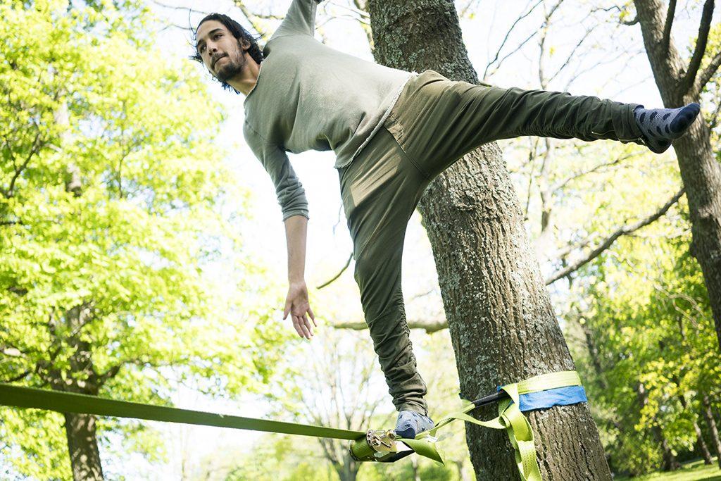 Mies tasapainoilee köyden päällä.