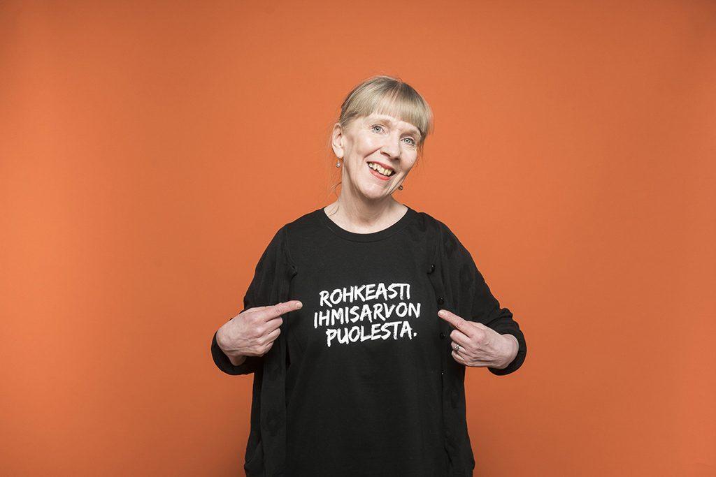 Heli Alkila osoittaa paitaansa, jossa lukee Rohkeasti ihmisarvon puolesta.