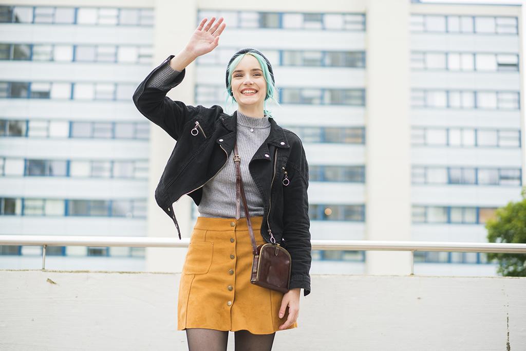 Nuori nainen seisoo kerrostalon pihalla ja vilkuttaa.
